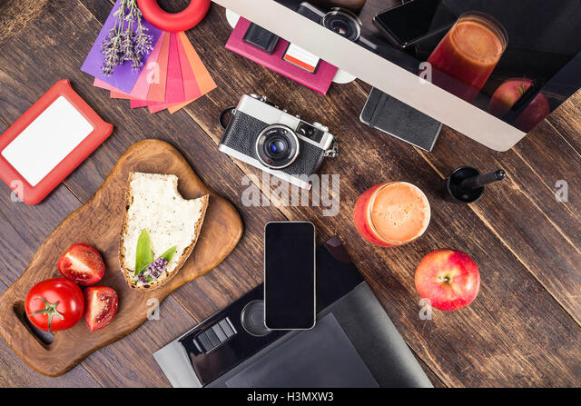 Overhead view of photo editing equipment; graphic tablet,  retro camera, smartphone, desktop computer and lunch - Stock Image