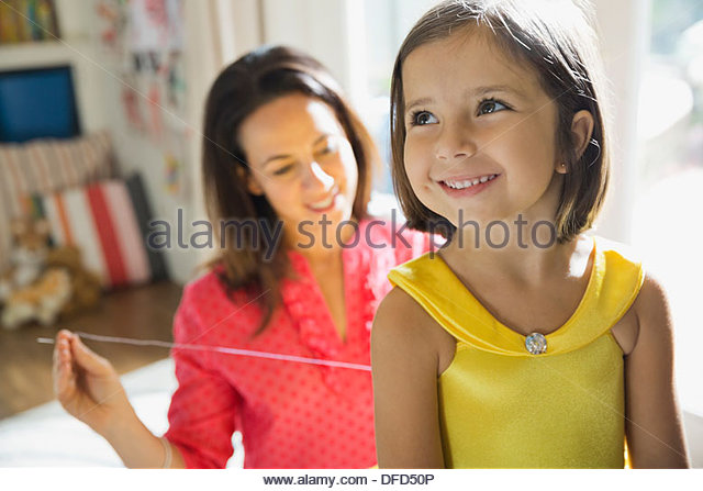 Smiling girl waiting for her mother to stitch costume together - Stock Image
