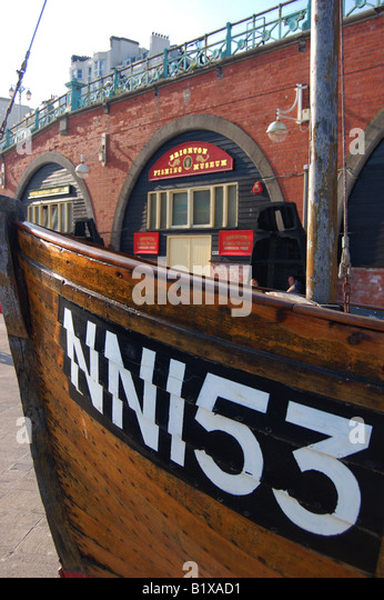 Fishing boat on Brighton sea front and shops, East Sussex, England - Stock Image