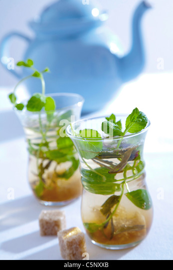 Green tea with minth leaves and brown sugar cubes - Stock Image