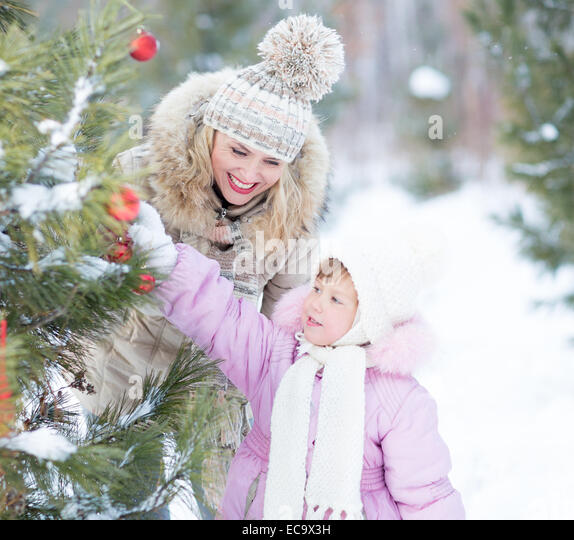 Happy family mother and child playing with christmas tree decoration outdoor - Stock-Bilder