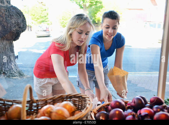 Two young women choosing food at market stall - Stock Image