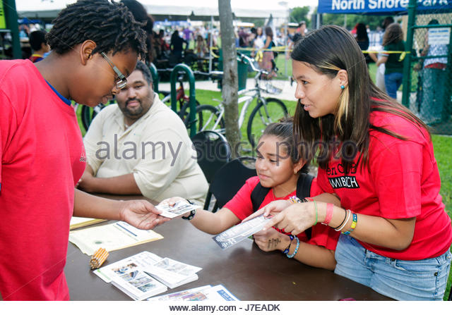 Miami Beach Florida North Beach Northshore Park Hispanic Heritage Festival teen girl information desk table volunteer - Stock Image