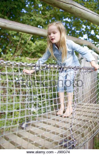 Young Girl Crossing Bridge In Adventure Playground - Stock-Bilder