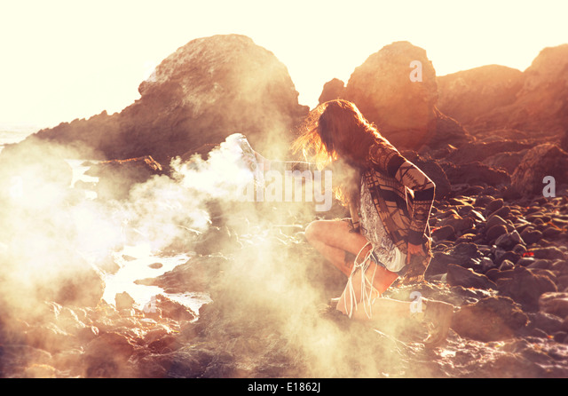 Smudge smoke offering on a rocky water seashore. - Stock Image