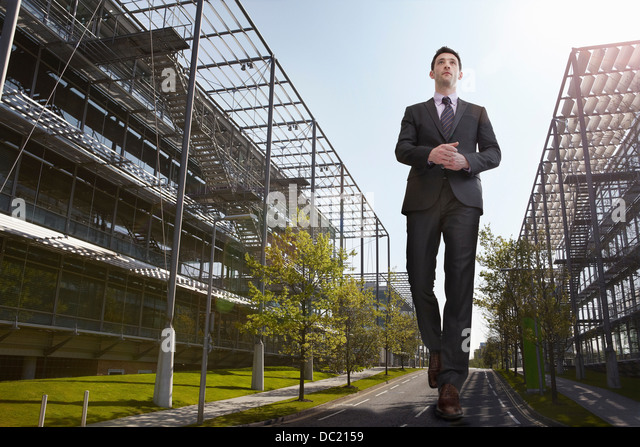 Oversized businessman walking on road, low angle view - Stock Image