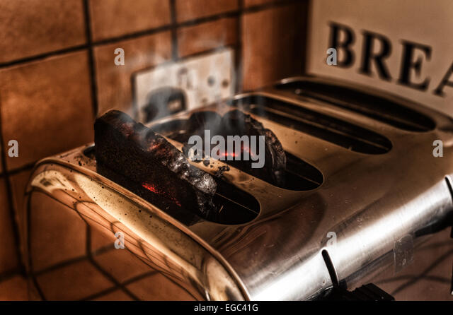 risk of fire smoking burning toast forgotten in the toaster in kitchen catching burning alight glowing red and charred - Stock Image
