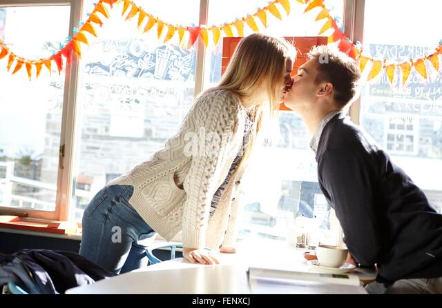 Romantic young couple kissing over in cafe table - Stock-Bilder