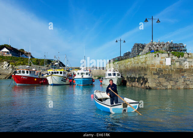 Man in dinghy, Newquay Harbour, Cornwall, England UK - Stock Image