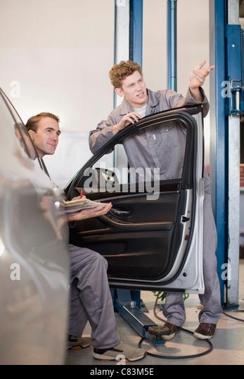 Mechanics working in garage - Stock Image