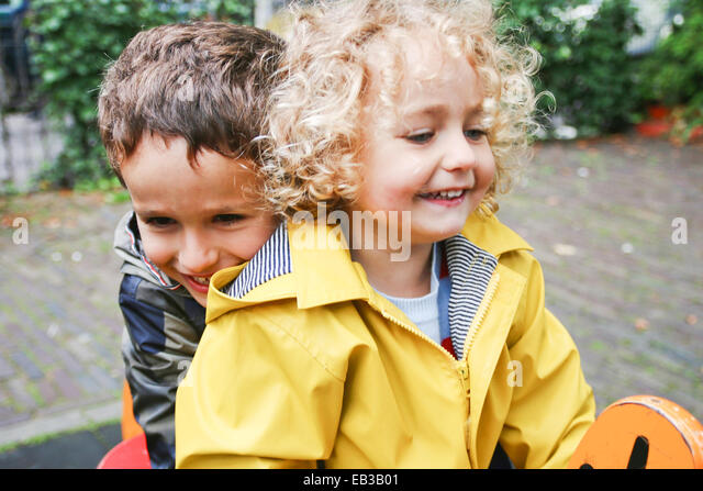 Netherlands, Amsterdam, Boy (4-5) and girl (2-3) playing outdoors - Stock Image