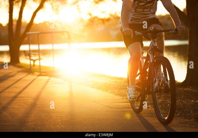 A depersonalized image of a male riding a mountain bike round a bay in Sydney Harbour in the evening - Stock Image