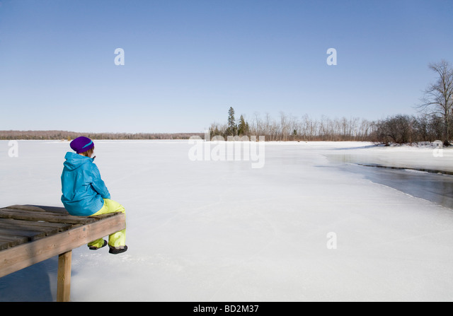 Woman Relaxing on Dock by Frozen Lake - Stock Image