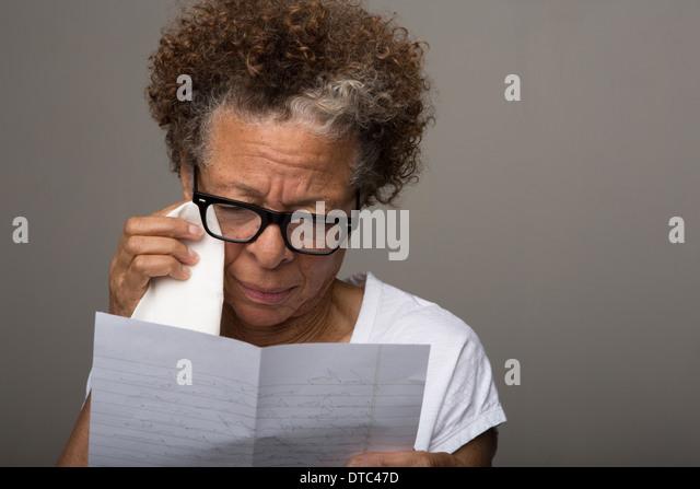 Studio portrait of sad senior woman reading a letter - Stock Image