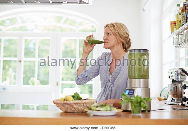 Woman drinking green vegan smoothie in kitchen - Stock Image