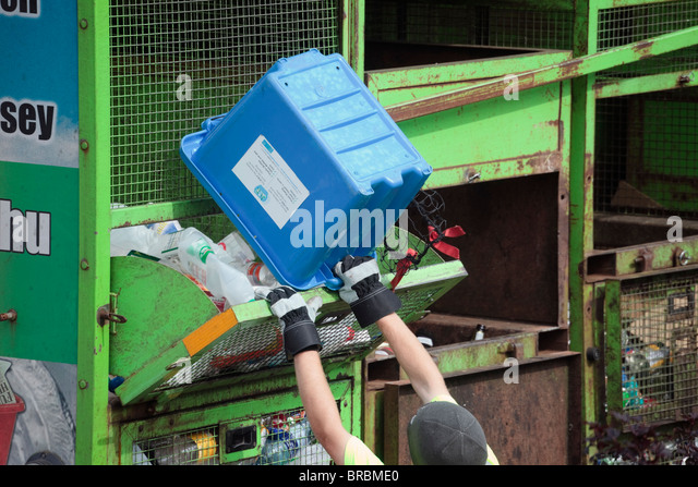 Workman collecting recycling emptying box of plastic bottles into truck as part of waste management scheme. UK - Stock Image