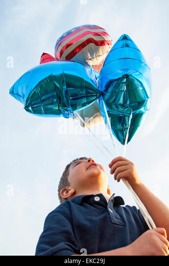 boy holding balloons - Stock Image