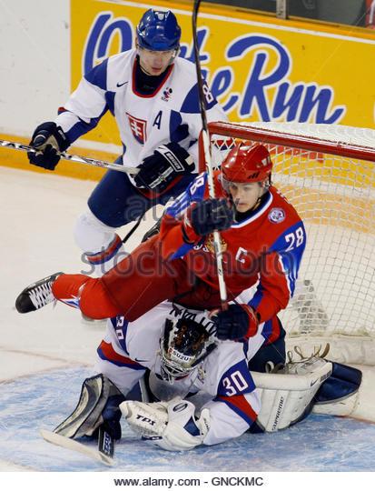 Russia's captain Nikita Filatov (middle) falls on Slovakia's goalie Zdenko Kotvan as Slovakia's Juraj - Stock Image