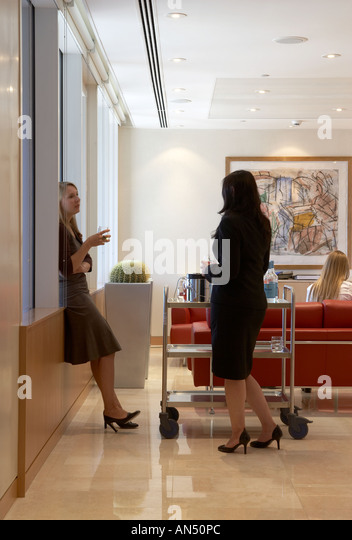 Office life and interiors part two. Employees in staff room talking. - Stock-Bilder