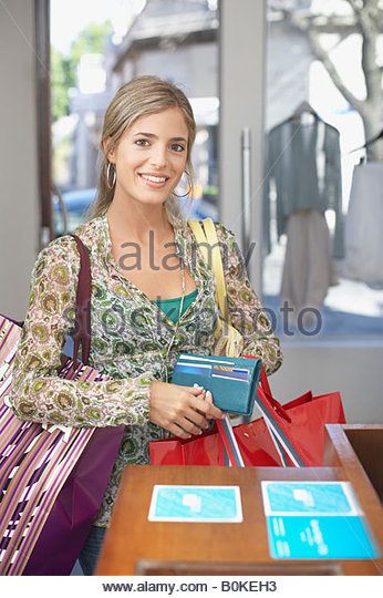 Woman in store holding wallet and shopping bags smiling - Stock Image