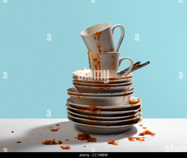 Studio shot of dirty, white dishes stacked - Stock Image
