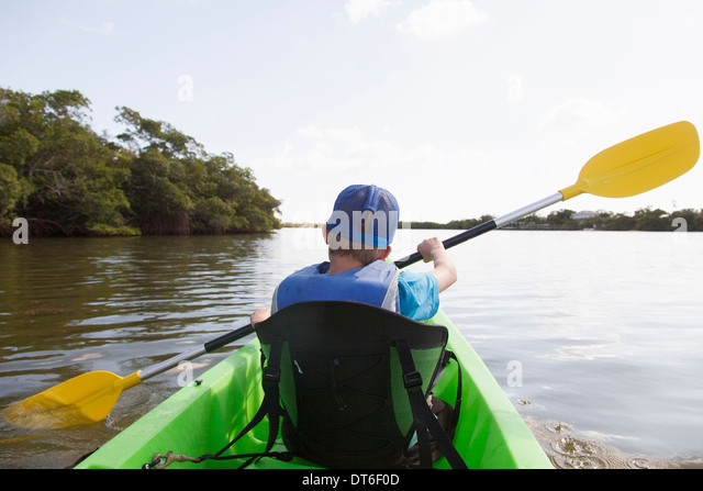 Young boy paddling canoe on tranquil river - Stock Image