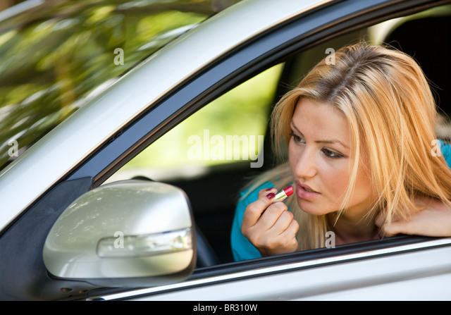 Young blonde woman applying makeup while in the car - Stock Image
