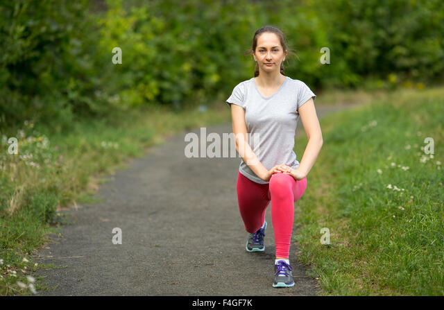 Young sporty girl warming up before Jogging in the Park. - Stock Image