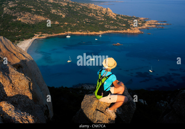 female hiker sittin on a rock over the bay of Roccapina, France, Corsica - Stock-Bilder