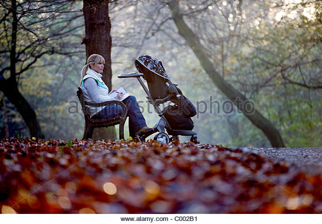 A young mother sitting on a bench, writing in a journal - Stock Image