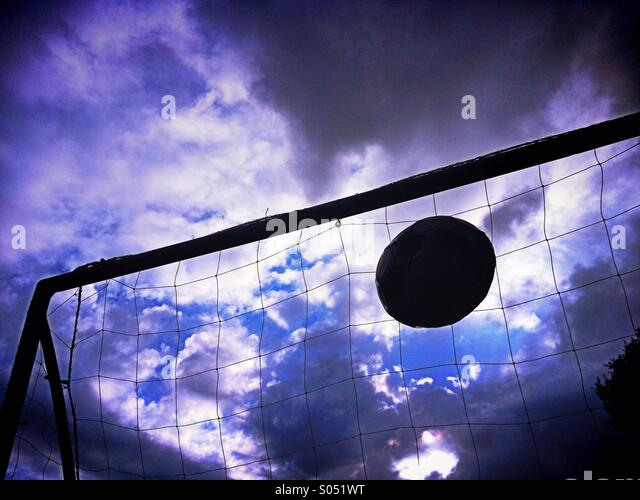Football flying into goal against dramatic sky - Stock Image