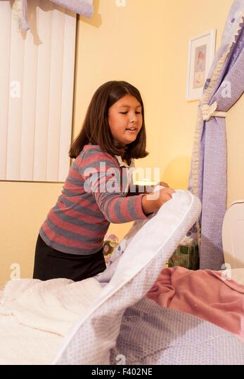 Korean American teen girl making her bed.   MR ©Myrleen Pearson - Stock-Bilder
