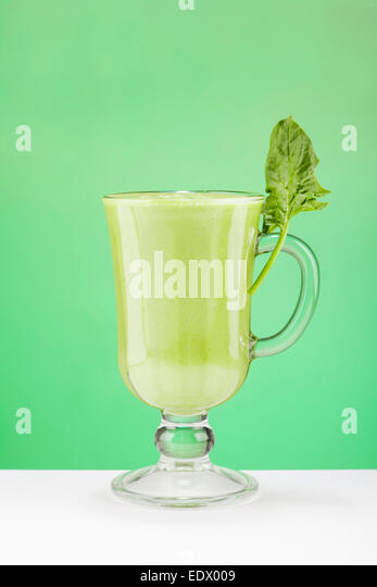 Green Smoothy in the glass on green background - Stock Image