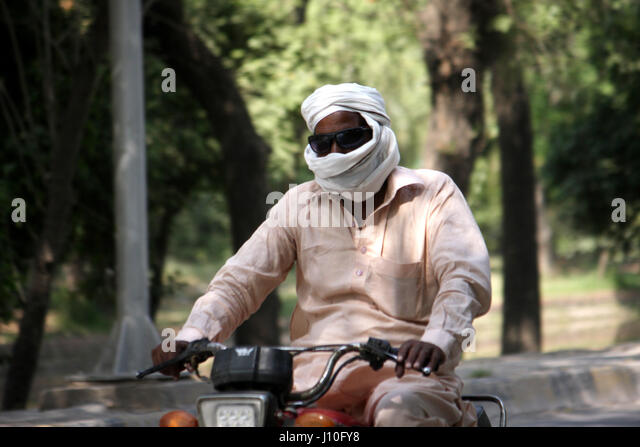 Lahore. 17th Apr, 2017. A man covers his face to protect himself during heat wave in eastern Pakistan's Lahore, - Stock Image