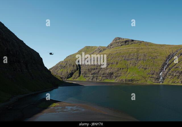 Helicopter flying over scenic lake - Stock-Bilder
