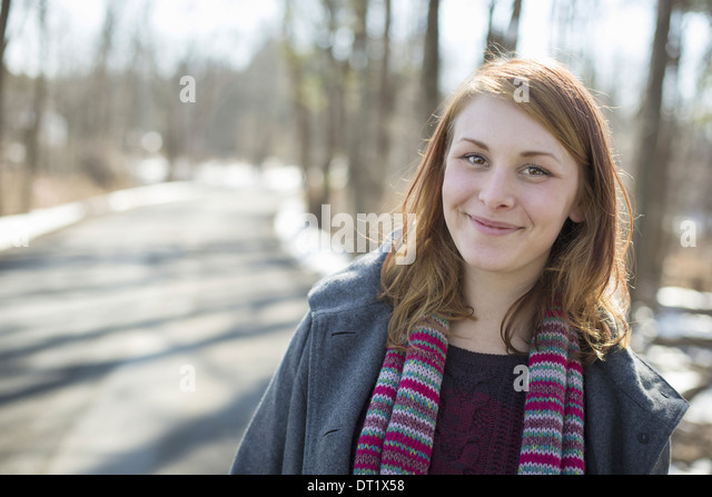 A young woman with a knitted scarf outdoors on a snowy winter day - Stock Image
