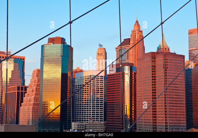 USA, New York City, Manhattan, Downtown Financial District City Skyline viewed from the Brooklyn Bridge at dawn - Stock Image