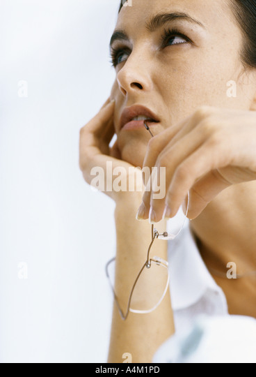 Woman holding head and biting on glasses - Stock Image