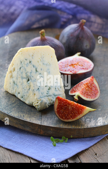 blue cheese and sweet fruit  figs on a wooden board - Stock Image