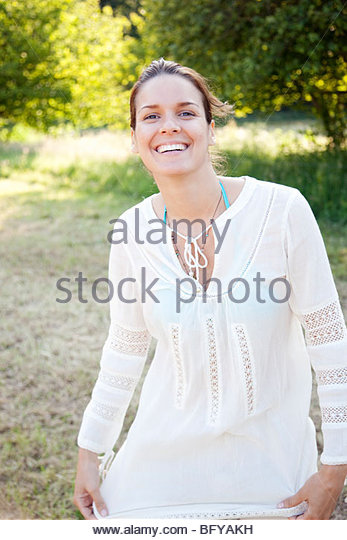 Portrait of woman smiling in countryside - Stock Image