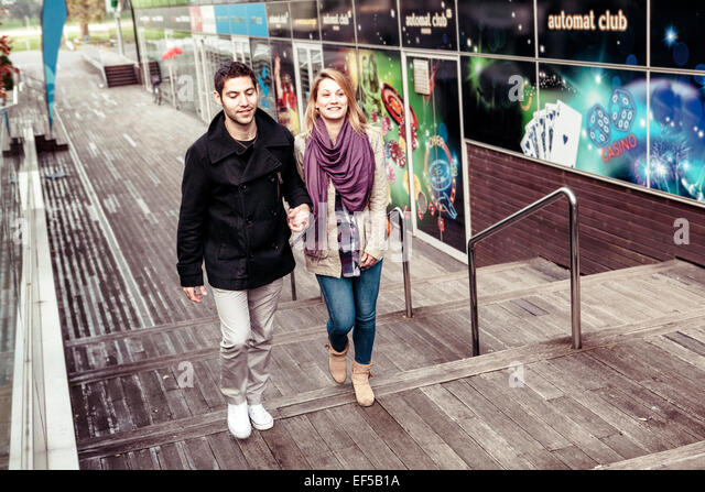 Happy young couple holding hands in town - Stock-Bilder