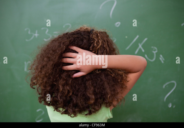 Schoolgirl thinking about algebra while scratching the back of her head - Stock-Bilder