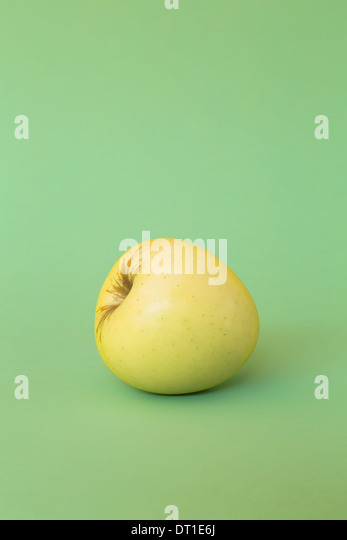 single Golden Delicious apple on green background - Stock Image