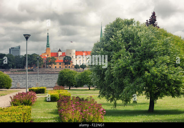 The wind in the leaves of the leaves of trees in a park on the waterfront in Riga against the backdrop of the Palace - Stock Image