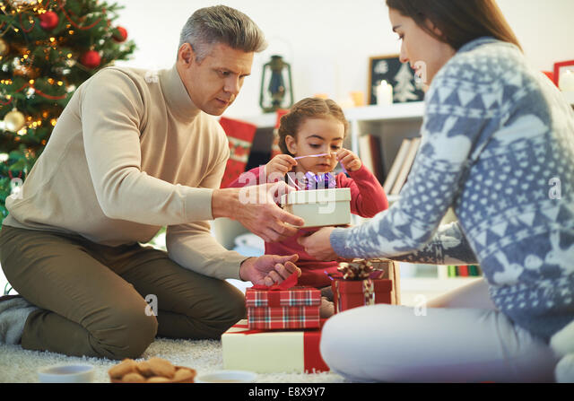 Modern family of three packing gifts before Christmas - Stock Image