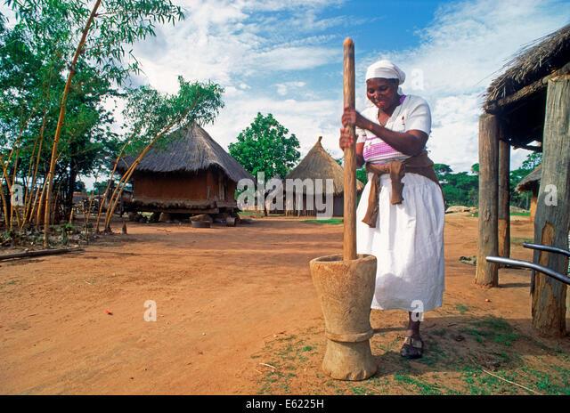 Woman pounding maize for cornbread in Zimbabwe village - Stock Image
