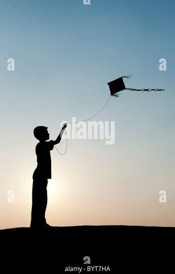 Young indian boy having fun flying a handmade paper kite in the indian countryside. Silhouette - Stock Image
