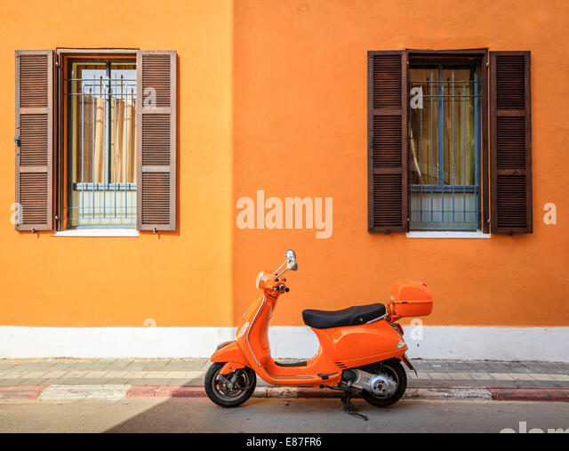 Scooter parked by the curb against orange building in Tel Aviv, Israel - Stock Image