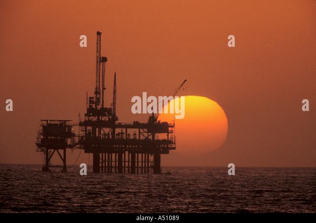 Offshore petroleum oil drilling platform with sunset in background California USA - Stock-Bilder