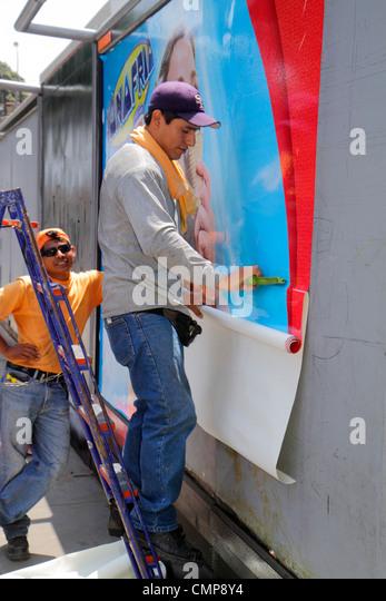 Lima Peru Barranco District Calle Rosello sidewalk scene vinyl billboard ad marketing installation ladder Hispanic - Stock Image